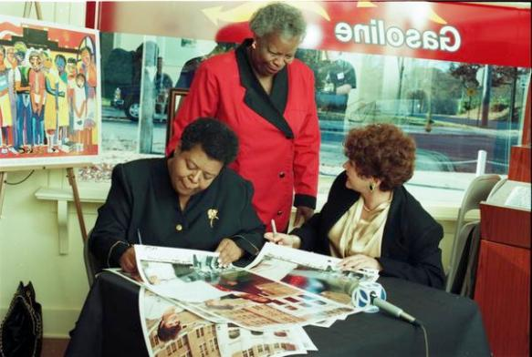 Elizabeth Eckford and Hazel Bryan sign posters of their famed picture 'reconciliation'